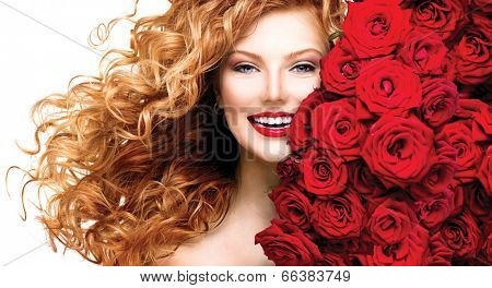 Beauty model girl with long curly red hair and beautiful red roses hairstyle. Fashion woman with blowing Wavy healthy hair isolated on white background