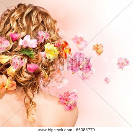 Hairstyle with colorful flowers. Beautiful healthy curly hair decorated with flowers.Over blurred pink background. Hair care concept. Backside view. Long permed hair style poster