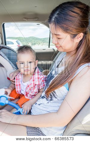 Asian Boy Sitting In The Car With His Mother