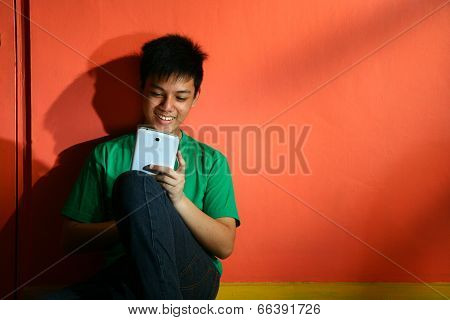Young asian teen with a tablet in a living room