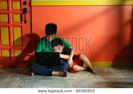 Young asian kids, brothers or siblings, with a laptop computer in a living room