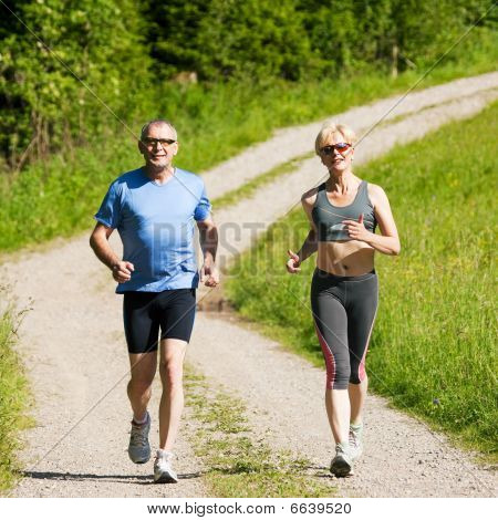 Mature or senior couple doing sport outdoors, jogging