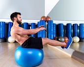 Fitball abdominal balance crunch Swiss ball man at fitness gym poster