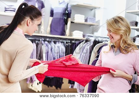 Aggressive girls fighting for red tanktop in department store