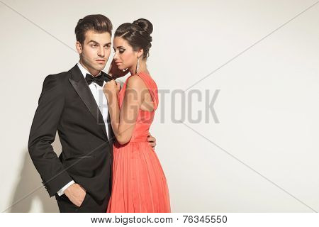 Picture of a young elegant couple posing, the man is looking away with one hand in his pocket, while his woman si embracing him.