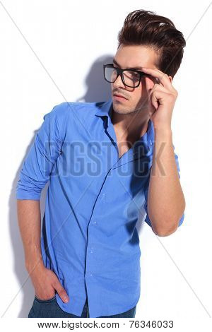 Attractive young business man looking away with one hand in his pocket while fixing his glasess. poster