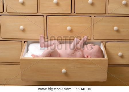 Cute One Month Old Baby Lying In A Drawer Of A Cabinet