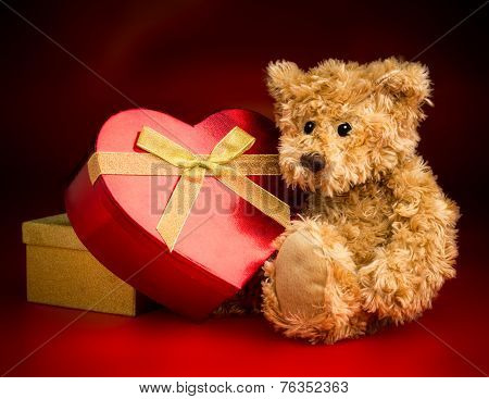 A Teddy Bear Hugging A Heart Shaped Box