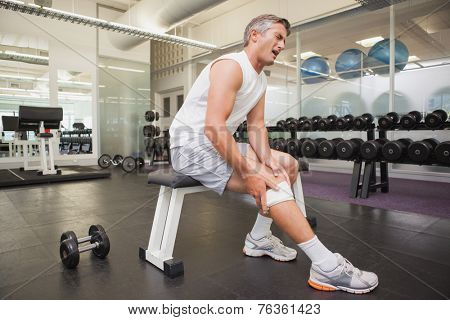 Injured man gripping his knee in the weights room at the gym