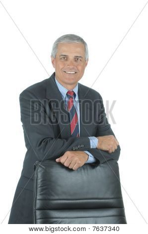 Smiling Businessman Leaning On Chair Back