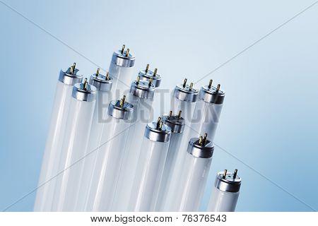 New fluorescent light tubes on blue background. Short depth-of-field.