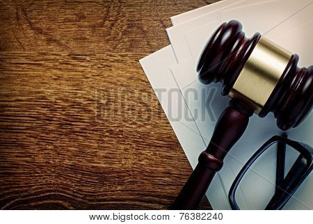 Wooden gavel with a brass band and glasses on notepaper conceptual of a judgement in law justice or an auctioneers gavel view from above on a wooden desk with copyspace poster