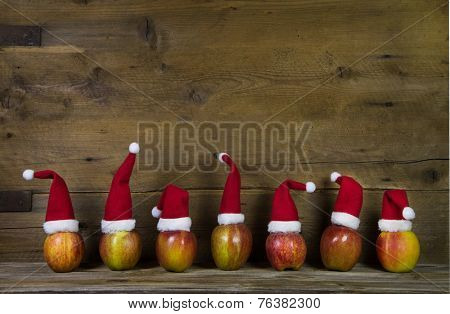 Decoration: Funny christmas greeting card with seven red santa hats on apples with wooden background.