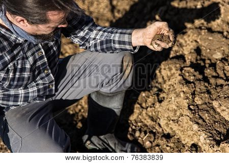 Close Up From A Farmer With Soil In His Hand