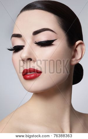 Portrait of young beautiful woman with stylish makeup. False eyelashes, black eyeliner and red lips poster