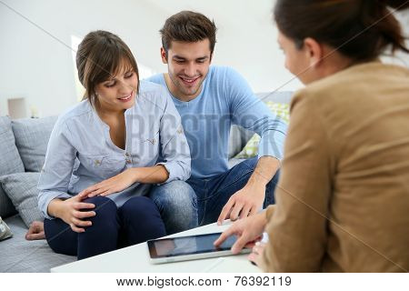 Young couple signing financial contrat on digital tablet