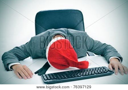 a man in suit with a santa hat sleeping in his desk after an office christmas party