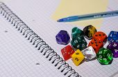 open exercise book with sticky card pen and role playing dices - stock photo poster