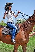 beautiful girl holding a gun and riding horse poster