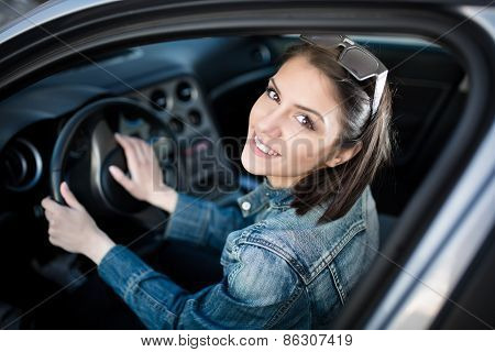 Happy woman in new car.Young woman in car going on road trip.Student driving car.Driver license exam
