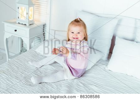 Funny And Cute Blond Little Laughing Girl Playing On Bed In Bedroom