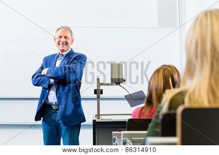 College professor giving lecture in college standing at desk