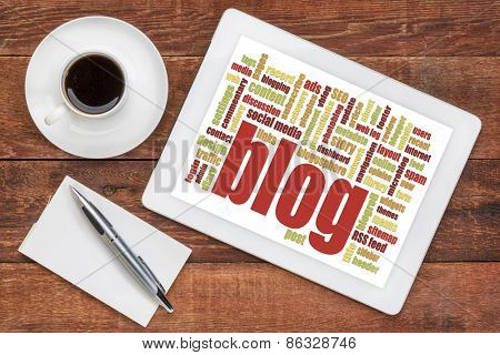blog word cloud on a digital tablet with a cup of coffee and note pad - internet concept