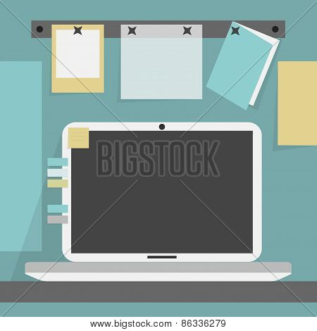 Open laptop on the desk and background wall with clipped papers and card
