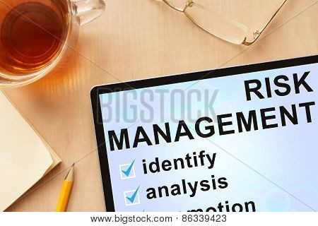 Tablet with words   risk management.