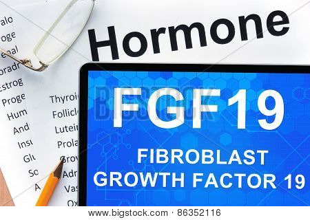 Papers with hormones list and tablet  with words fibroblast growth factor 19 (FGF19) .