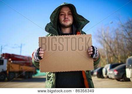 Homeless person with blanck cardboard. Focused on cardboard