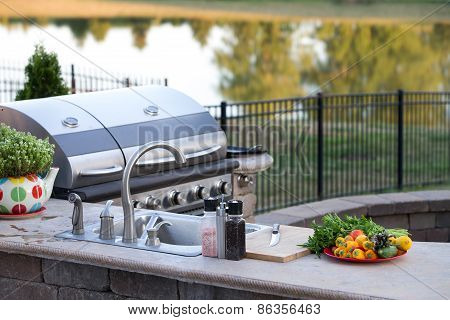 Preparing a healthy summer meal in an outdoor kitchen with gas barbecue and sink on a brick patio overlooking a tranquil lake with tree reflections poster