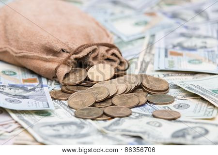 Golden dollar coins spilling from a hessian bag onto a background of US dollar bills with focus to the coins conceptual of wealth winnings growth returns success graft or money laundering concept poster