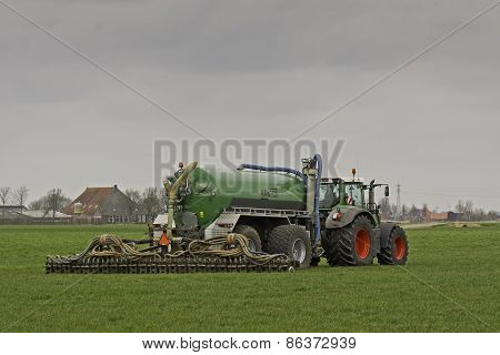 Tractor injects liquid manure in a meadow