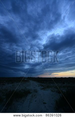 dark storm clouds above sand road in steppe landscape at sunset