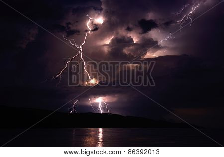 lightnings at seaside striking on island with stormy clouds