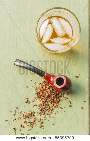 Tobacco pipe on rustic warn green wood surface with spilled natural tobacco and a glass of whisky on the rocks poster
