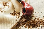 Tobacco pipe on rustic warn wood surface with spilled natural tobacco poster