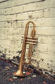 Old worn trumpet stands alone against a grungy pealing white brick wall outside a jazz club poster