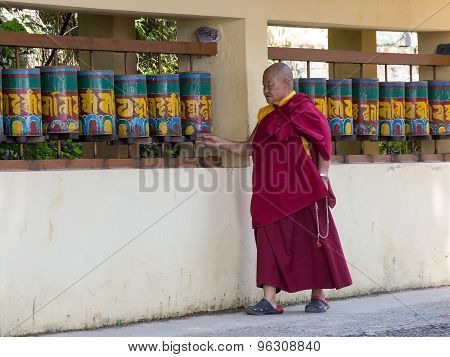 Old Tibetan Buddhist Monk Turning The Prayer Wheels At Temple In The Dharamsala, India