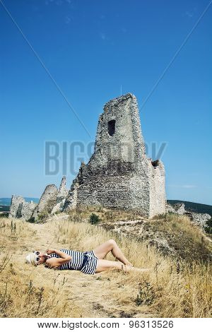 Young Woman In A Sailor Outfit Lying On The Dry Grass And Behind Is The Castle Cachtice