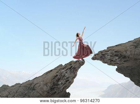 Young woman in evening dress walking over mountain gap