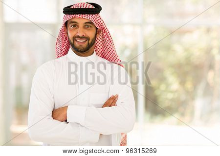 smiling arabian man with arms crossed