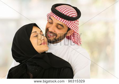 lovely young muslim couple cuddling at home