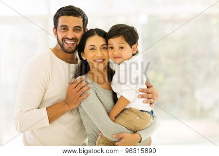 portrait of happy indian family of three standing indoors
