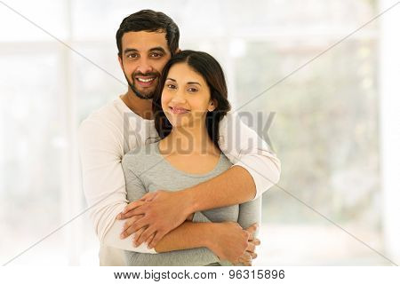 romantic indian couple hugging at home