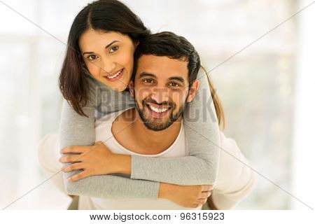 happy young indian couple having fun with piggyback indoors