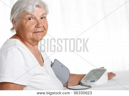 Elder Woman Measuring Blood Pressure With Automatic Manometer