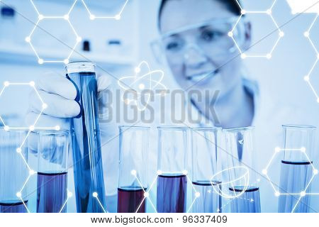 Science graphic against attractive redhaired female holding a test tube