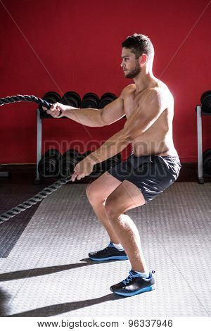 Muscular man exercising with rope in crossfit gym